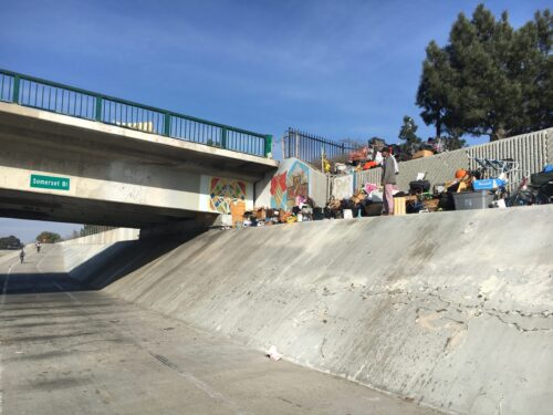 A homeless guy living with all his junk on a cement ledge overlooking the trail under Somerset.
