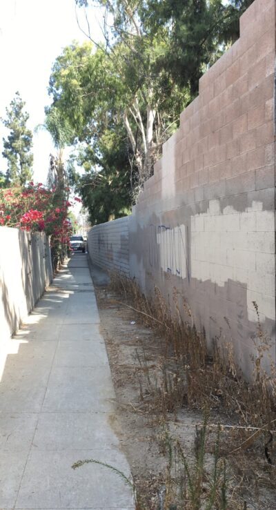 Unmarked narrow paved foot path that goes a hundred yards, to a street called Nobles Avenue.