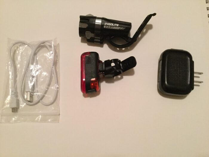 What I use is a set of rechargeable Bontrager lights that I bought at Bike Zone. Both these lights come with a cable that can be plugged into a computer USB. Or an old phone charger such as the one I use on the right.