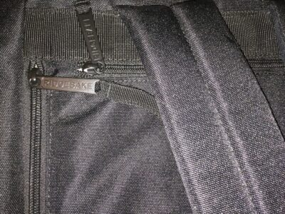 Metal zipper tabs with name, located on the hidden compartment on the backside, and the main compartment on the side.